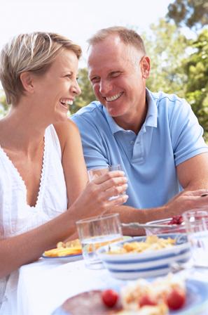 szczęśliwa, uśmiecjnięta para siedząca przy śniadaniu na świeżym powietrzu