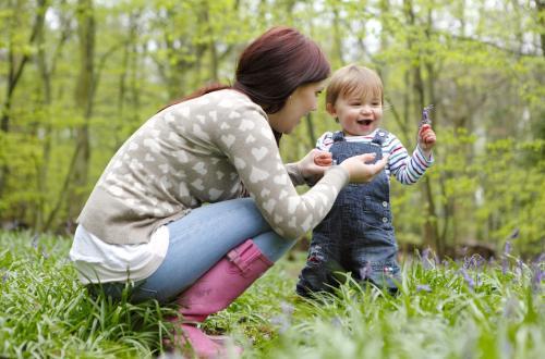 mama karmi dziecko ze słoiczka na polanie w lesie