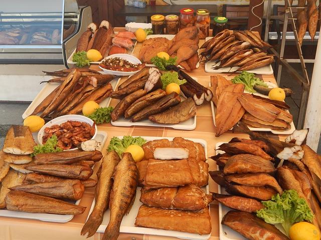 ryby wędzone różne rodzaje wyłożone na stół, przeznaczone do sprzedaży