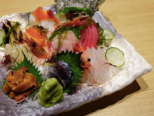 surowe ruby i krewetki podane na talerzu z masy perłowej udekorowane imbirem kawiorem i wasabi