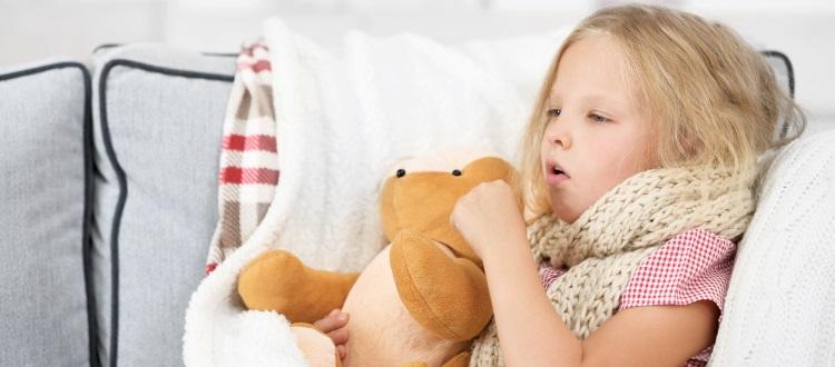 mała dziewczynka kaszle owinięta szalikiem
