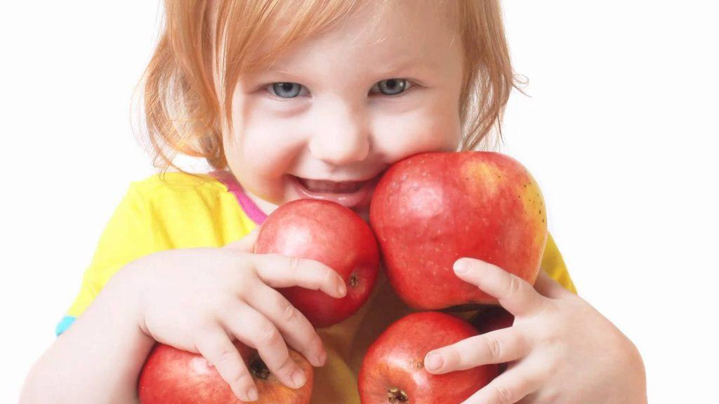 uśmiechnięte dziecko trzyma jabłka