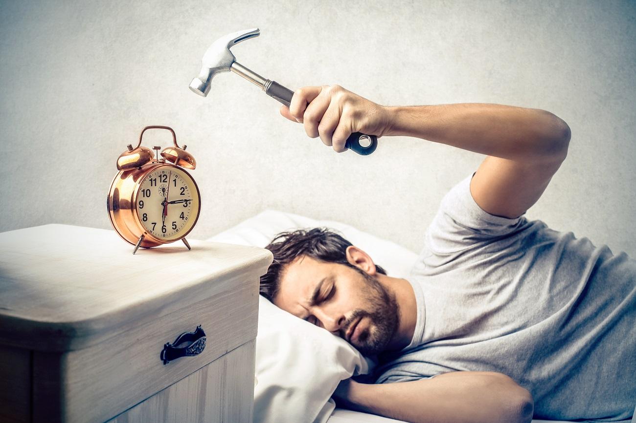 częściowo jeszcze mężczyzna próbuje rozbić z zamkniętymi oczami leżąc w łóżku budzik młotkiem - jak wstawać rano