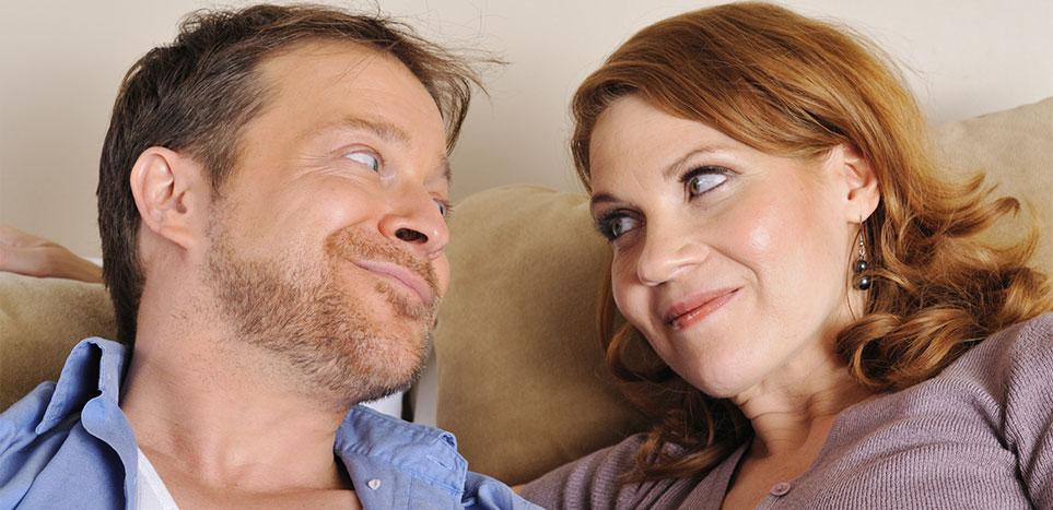 zadowolony mężczyzna i kobieta siedzą na kanapie i uśmiechają się bo mają środki na potencje dla mężczyzn