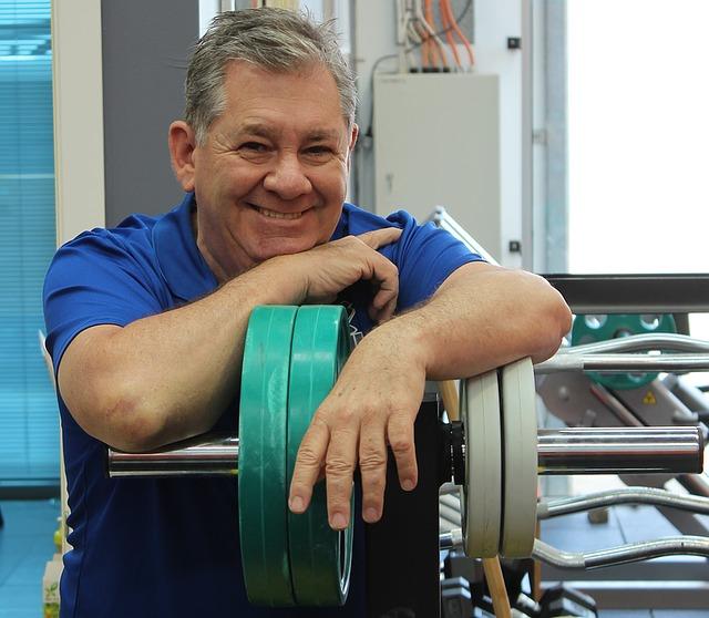 mężczyzna oparty z uśmiechem o sztangę wykonuje trening indywidualny
