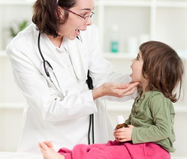 pani doktor sprawdza gardło małej dziewczynki pod kontem zapalenia górnych dróg oddechowych