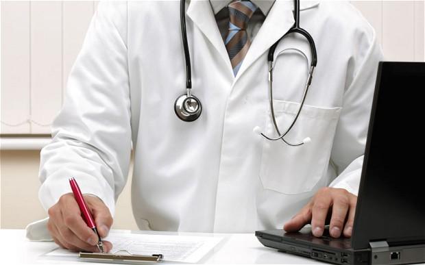 jak znaleźć dobrego ginekologa - lekarz w kitlu przy biurku z przewieszonym stetoskopem zapisuje historię choroby pacjentki