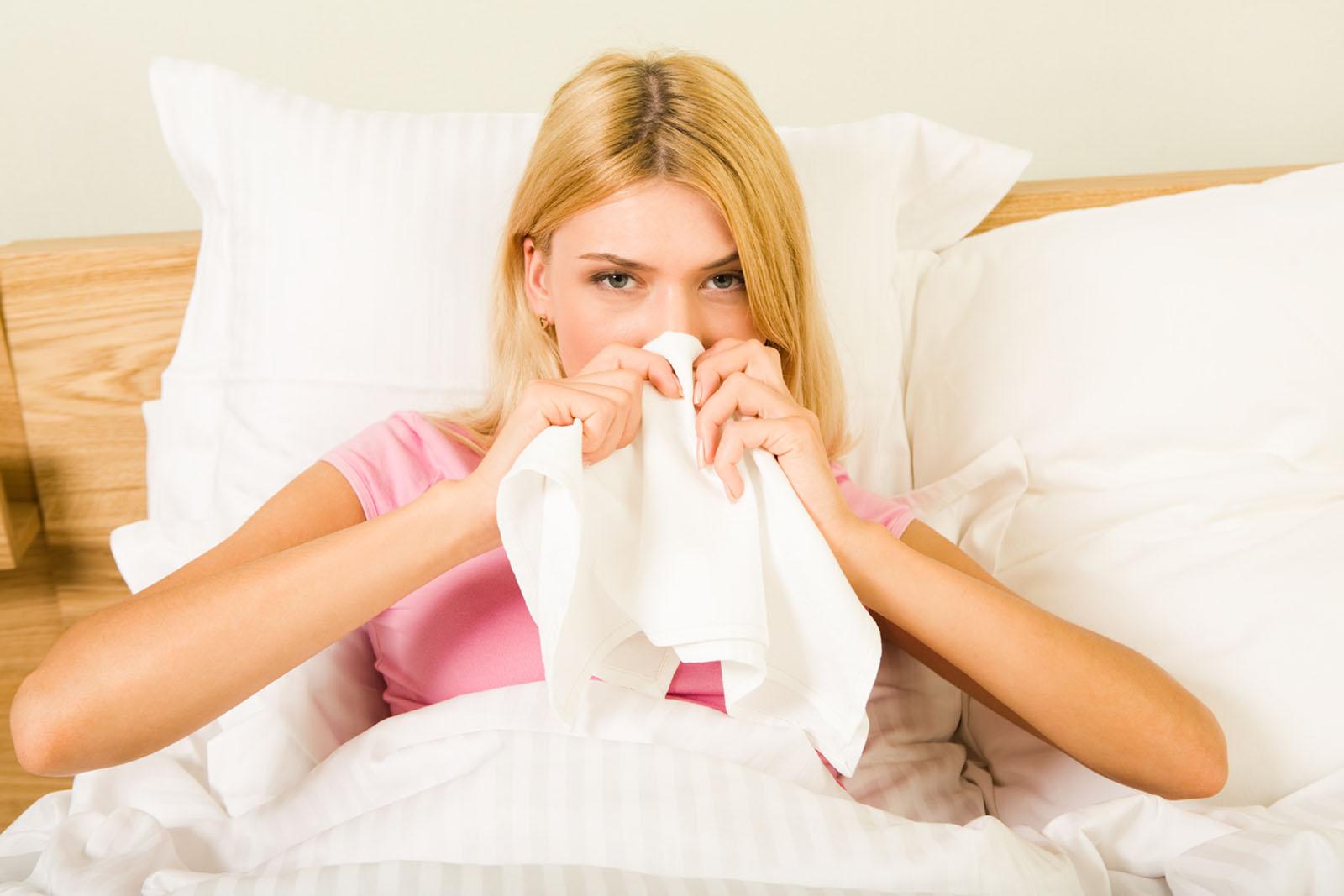 młoda dziewczyna ma katar bakteryjny i leży w łóżku z chusteczką przy nosie