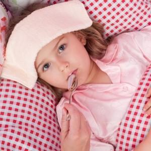 mała chora dziewczynka leży w pościeli w różową kratkę w okładem z ręcznika na czole