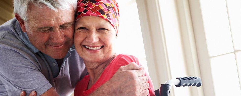 uśmiechnięta para seniorów. Starszy mężczyzna przytula chorą na nowotwór ale uśmiechniętą starszą kobietę