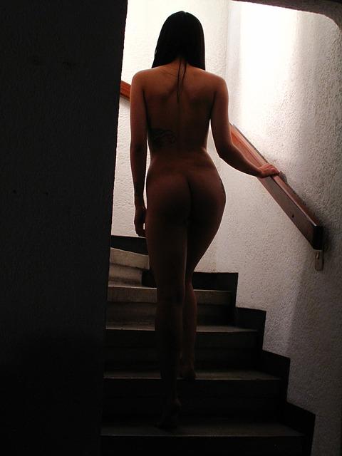 goła kobieta wchodzi po schodach
