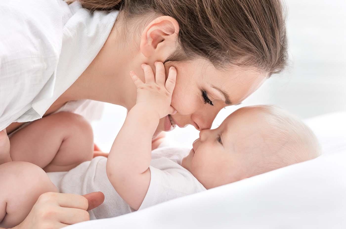 jak leczyć biegunkę u dziecka - szczęśliwa młoda mam przytula swoje niemowlę